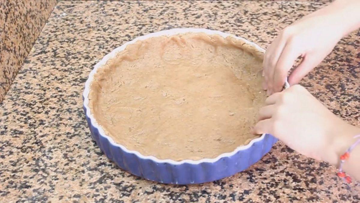 extender la masa de la torta de manzana con las manos en el molde